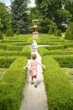 Glückliche Kinder, die durch das Labyrinth laufen Stockfotos