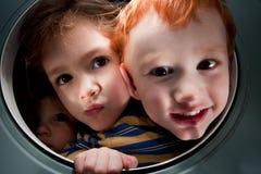 Glückliche Kinder, die durch Fensteröffnung schauen Lizenzfreies Stockfoto