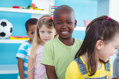 Glückliche Kinder, die in einer Linie stehen Stockfotografie