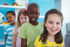 Glückliche Kinder, die in einer Linie stehen Lizenzfreie Stockfotos