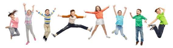 Glückliche Kinder, die in einer Luft über weißem Hintergrund springen lizenzfreie stockfotografie