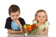 Glückliche Kinder, die Gemüse essen Stockfotografie