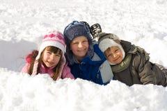 Glückliche Kinder, die im frischen Schnee spielen Stockbilder