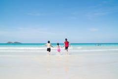 Glückliche Kinder, die im Ozean spielen lizenzfreies stockbild