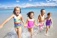 Glückliche Kinder, die im Ozean spielen und spritzen Lizenzfreies Stockbild