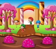 Glückliche Kinder, die im Süßigkeitsland spielen Stockbild