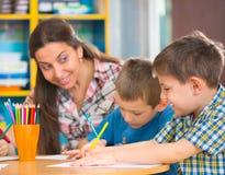 Glückliche Kinder, die am Kindergarten zeichnen stockfotos