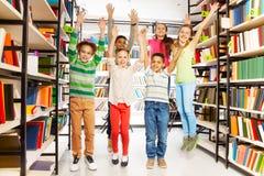 Glückliche Kinder, die mit den Händen oben in der Bibliothek springen Lizenzfreie Stockbilder