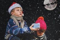 Glückliche Kinder, die mit Schneeflocken auf Winterweg spielen Lizenzfreies Stockfoto