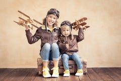 Glückliche Kinder, die mit Spielzeugflugzeug spielen lizenzfreie stockfotografie
