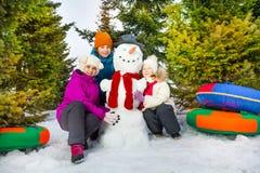 Glückliche Kinder, die nah an nettem Schneemann sitzen Stockfoto
