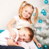 Glückliche Kinder, die nahe Weihnachtsbaum streicheln Stockfotografie