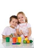 Glückliche Kinder, die Ostereier färben stockfotografie