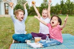 Glückliche Kinder, die Picknick auf Rasen genießen lizenzfreie stockfotos
