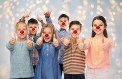 Glückliche Kinder, die sich Daumen am roten Nasentag zeigen lizenzfreie stockfotos