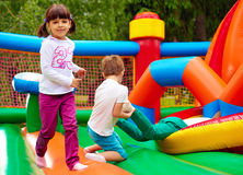 Glückliche Kinder, die Spaß auf aufblasbarem Anziehungskraftspielplatz haben Lizenzfreies Stockbild