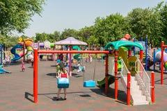 Glückliche Kinder, die Spaß auf Spielplatz haben Stockbilder