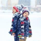Glückliche Kinder, die Spaß mit Schnee im Winter haben lizenzfreie stockbilder