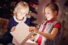 Glückliche Kinder, die Weihnachtsgeschenk öffnen Stockfotos