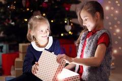 Glückliche Kinder, die Weihnachtsgeschenk öffnen Stockfoto