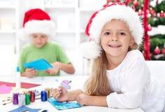 Glückliche Kinder, die Weihnachtskarten bilden Stockfotografie