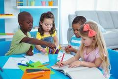 Glückliche Kinder, die zusammen Künste und Handwerk genießen Stockbild