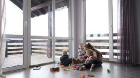Glückliche Kinder, die zusammen spielen Kinderkonzept Kinder im Privathaus mit den panoramischen Fenstern, die auf dem Boden sitz stock footage