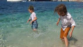 Glückliche Kinder freuen sich und spielen im Meerwasser Kinder sind naß und, Feiertage mit Kindern, Schulferien glücklich stock video