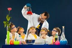 Glückliche Kinder mit dem Wissenschaftler, der Wissenschaft tut, experimentiert im Labor stockfoto
