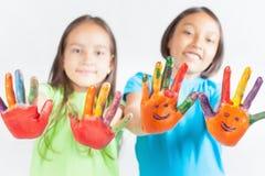 Glückliche Kinder mit den gemalten Händen Der Tag der internationale Kinder Stockfotos