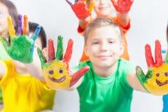 Glückliche Kinder mit den gemalten Händen Der Tag der internationale Kinder Stockfotografie
