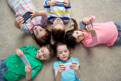 Glückliche Kinder mit den Smartphones, die auf Boden liegen Stockfotos