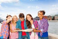 Glückliche Kinder mit der Karte, die zusammen steht Lizenzfreie Stockfotografie
