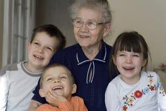 Glückliche Kinder mit Großmutter Stockfoto
