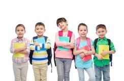 Glückliche Kinder mit Schultaschen und Notizbüchern Lizenzfreies Stockfoto