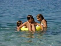 Glückliche Kinder mit Strandspielwaren auf Meer Lizenzfreies Stockfoto