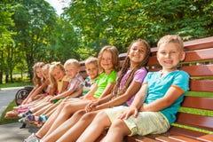 Glückliche Kinder sitzen auf der Bank im Park Lizenzfreies Stockfoto