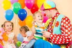 Glückliche Kinder und Clown auf Geburtstagsfeier Lizenzfreies Stockfoto