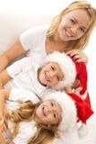Glückliche Kinder und Frau, die zur Weihnachtszeit sich entspannt Stockfotografie