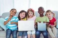 Glückliche Kinder unter Verwendung der Technologie beim Sitzen lizenzfreie stockbilder