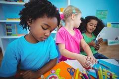 Glückliche Kinder unter Verwendung des Lehms zusammen modellieren Stockbild