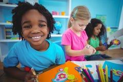 Glückliche Kinder unter Verwendung des Lehms zusammen modellieren Stockbilder