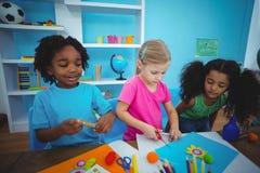 Glückliche Kinder unter Verwendung des Lehms zusammen modellieren Lizenzfreie Stockfotografie