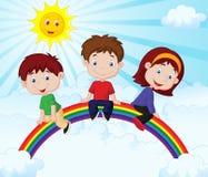 Glückliche Kinderkarikatur, die auf Regenbogen sitzt Lizenzfreies Stockfoto