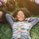 Glückliche Kinderkinder, die auf Gras legen lizenzfreies stockbild