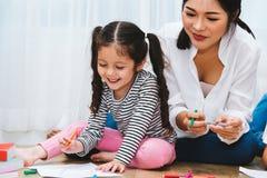 Glückliche Kinderkindermädchensohn-Kindergartenzeichnung auf peper Lehrer e Stockfotos
