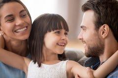 Glückliche Kindertochter, welche die Eltern betrachten lächelnde Mutter umfasst lizenzfreie stockbilder