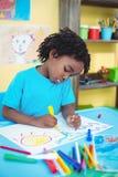 Glückliche Kinderzeichnung auf seinem Blatt Lizenzfreie Stockfotografie