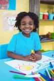 Glückliche Kinderzeichnung auf seinem Blatt Stockfotos