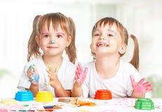 Glückliche Kinderzwillinge zeichnet Farben, erhalten schmutzig lizenzfreies stockbild